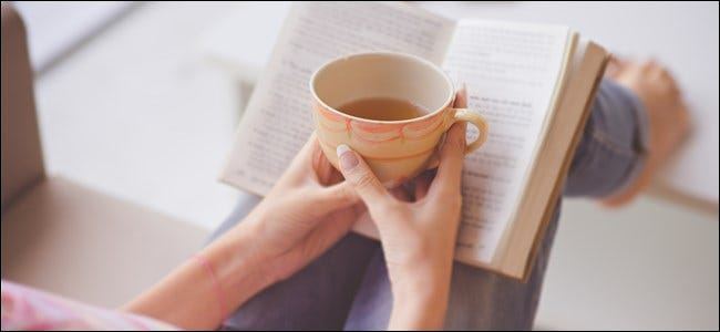 A woman's hands holding a mug of tea over an open book.