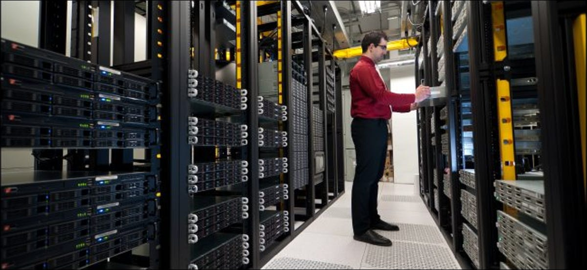 An IT administrator installing a rack-mounted server in a data center.