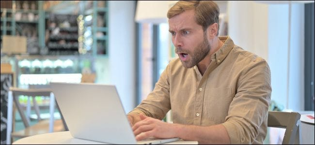A man looking at his laptop with a shocked expression.