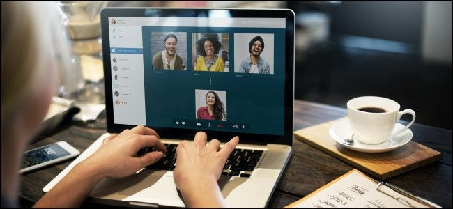 A woman's hands on the keyboard of her laptop, with four people in a video-conference call on the screen.