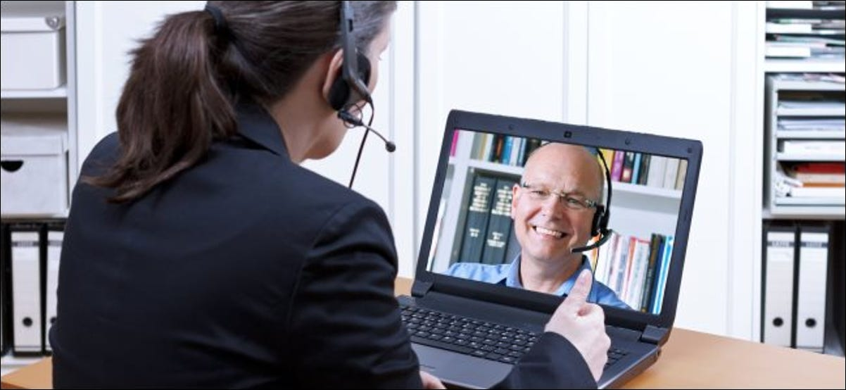 A woman video-conferencing with a man on a laptop.