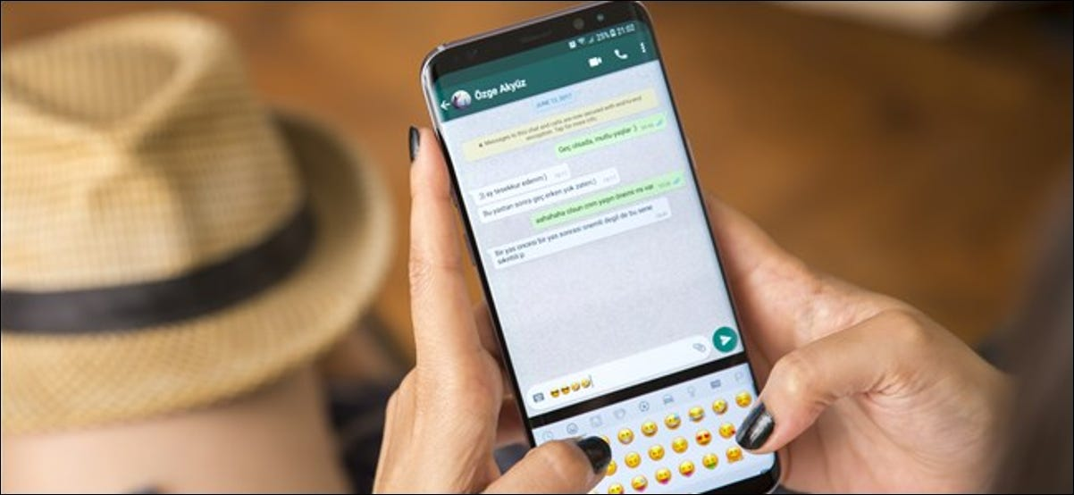 A woman's hands holding a smartphone and typing emojis in WhatsApp.