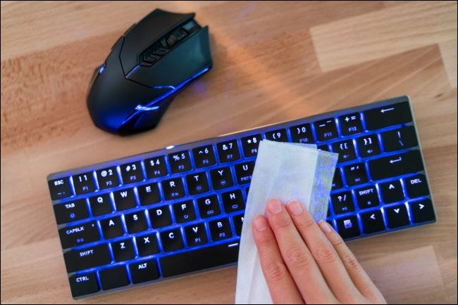 A hand wiping a detached keyboard.