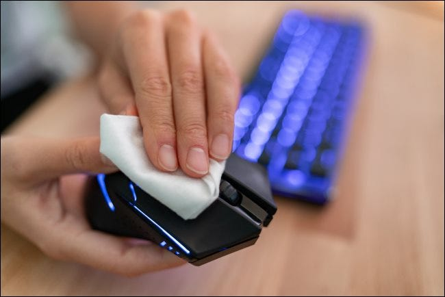 A hand wiping a computer mouse with a cloth.