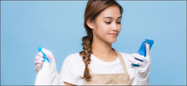 A young woman using a smartphone while holding cleaning products.