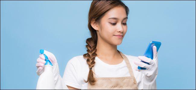 Una mujer joven que usa un teléfono inteligente mientras sostiene productos de limpieza.