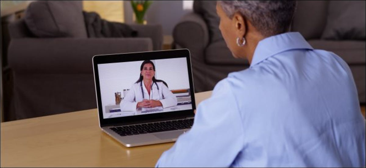 An older woman talking to a doctor on a laptop