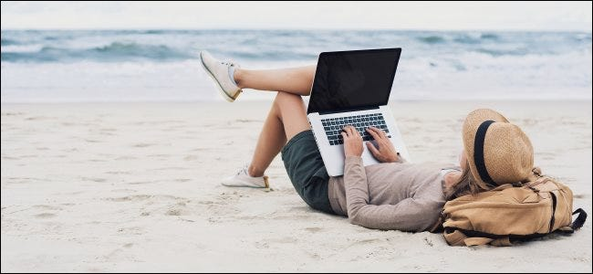 A woman using a laptop computer while laying on a beach.