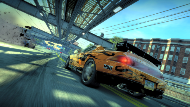 "A yellow sports car driving on a highway under an overpass in ""Burnout Paradise Remastered."""