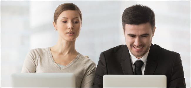 A woman looking over a coworker's shoulder and spying while he uses a laptop computer.