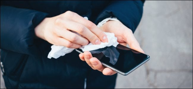 Hands holding and wiping a smartphone screen with a cloth.