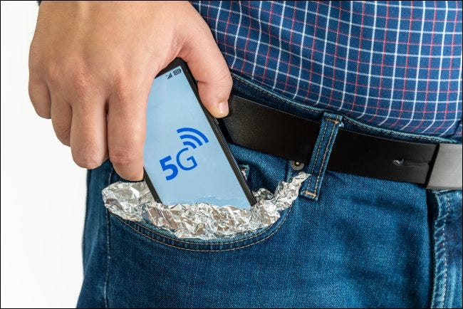 A man putting a 5G smartphone into his tin-foil-covered pocket.