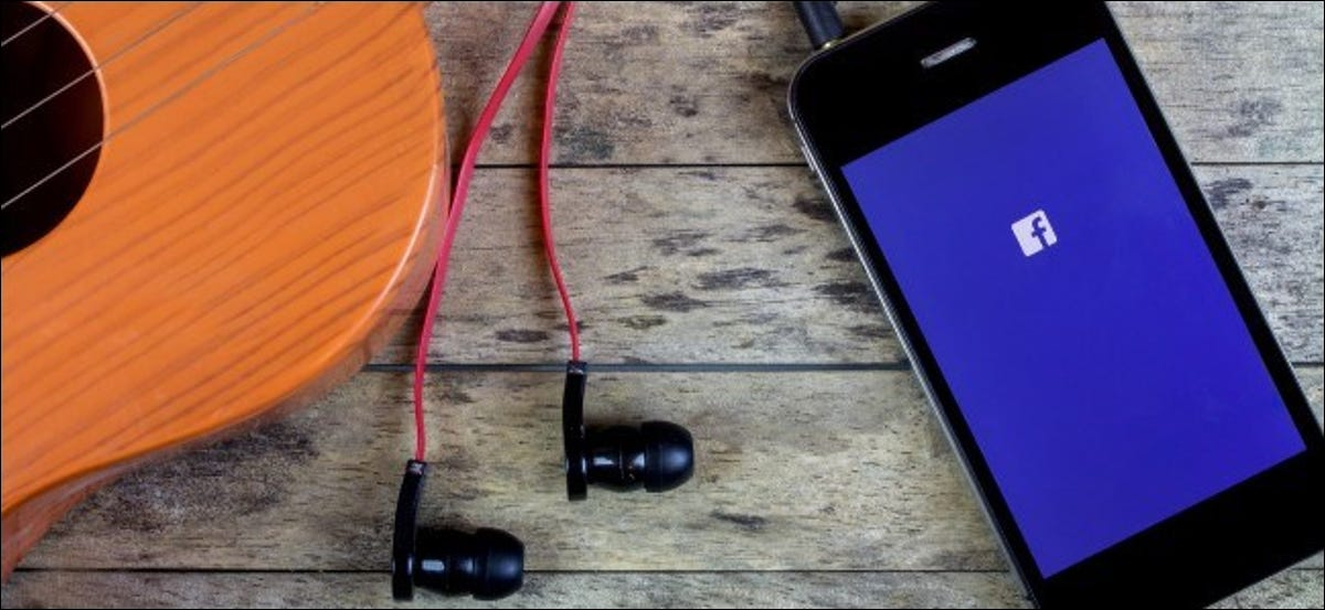 Facebook logo on a smartphone with earbuds connected to it.