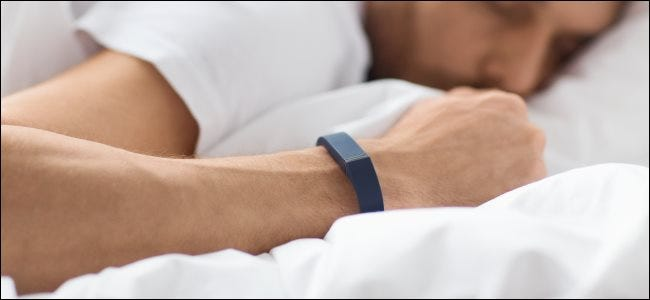 A man wearing an activity tracker on his wrist while sleeping in bed.