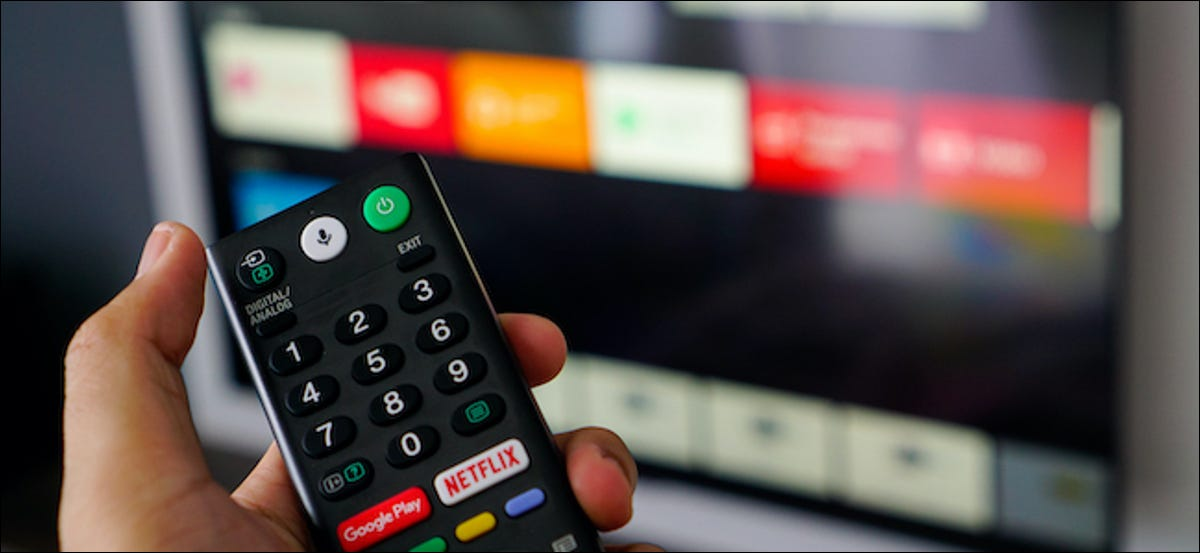 An Android TV remote with the TV interface in the background.