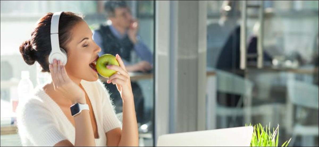 Uma mulher usando fones de ouvido enquanto usa um Apple Watch e come uma maçã.