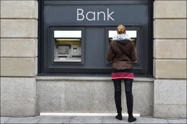 A woman using an outdoor ATM.