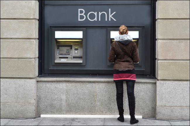 A woman using an outdoor ATM.