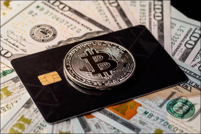 Ένα φυσικό διακριτικό Bitcoin πάνω από μια πιστωτική κάρτα με 100 $ λογαριασμούς.