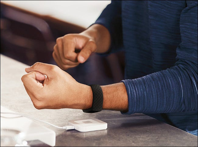A man charging a Fitbit Charge 4.