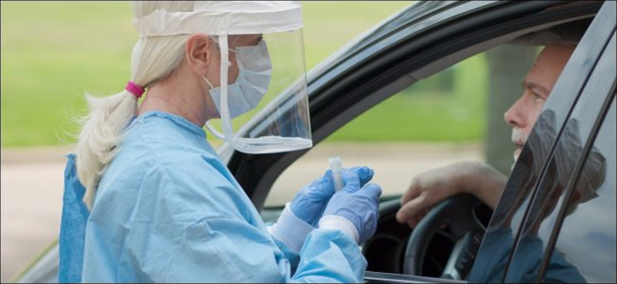A woman wearing a full mask, medical gown, and gloves holding a vial, and talking to a man sitting in a car.