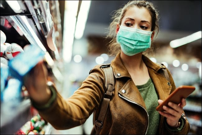 A woman wearing a face mask and holding a phone while taking something off a store shelf.