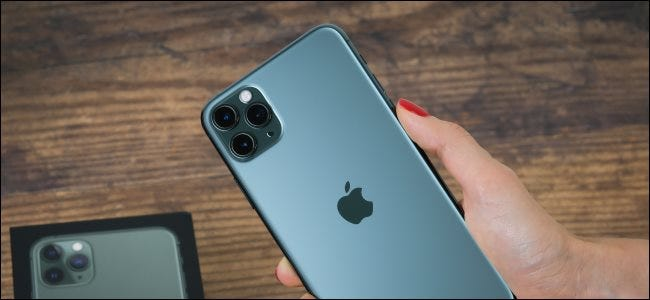 A hand holding an iPhone 11 Max Pro and showing off the back with the camera.