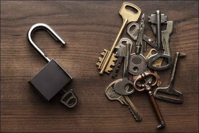 Multiple keys next to an open padlock.