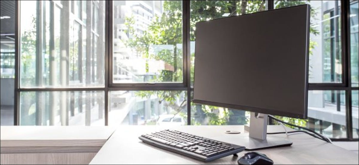 A desktop computer monitor, keyboard, and mouse on a desk.