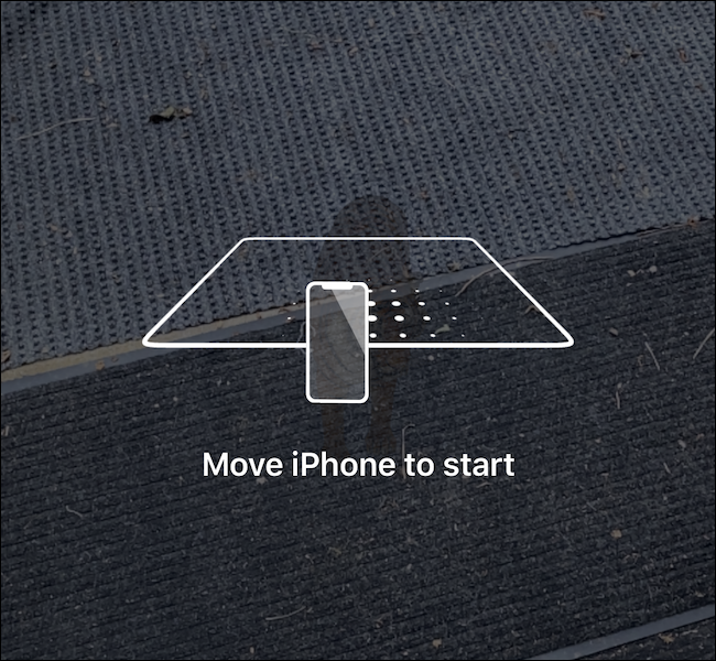 A phone scanning the ground to load the AR experience.