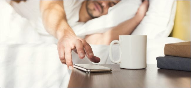 A sleepy man in bed reaching for a smartphone on a nightstand.