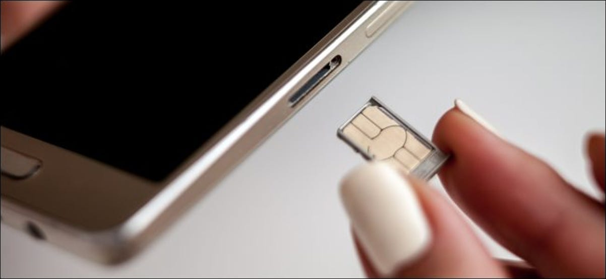Fingers swapping a smartphone's SIM card.