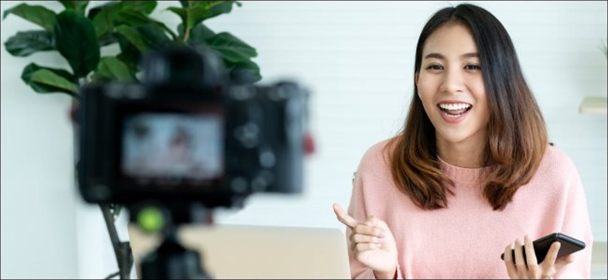 A woman filming a video on a camera in front of a laptop.