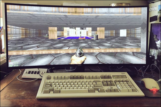 """""""Doom"""" on a widescreen monitor behind a desktop keyboard and mouse."""