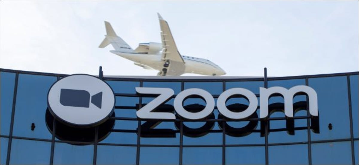 An airplane flying over a building with the Zoom logo.