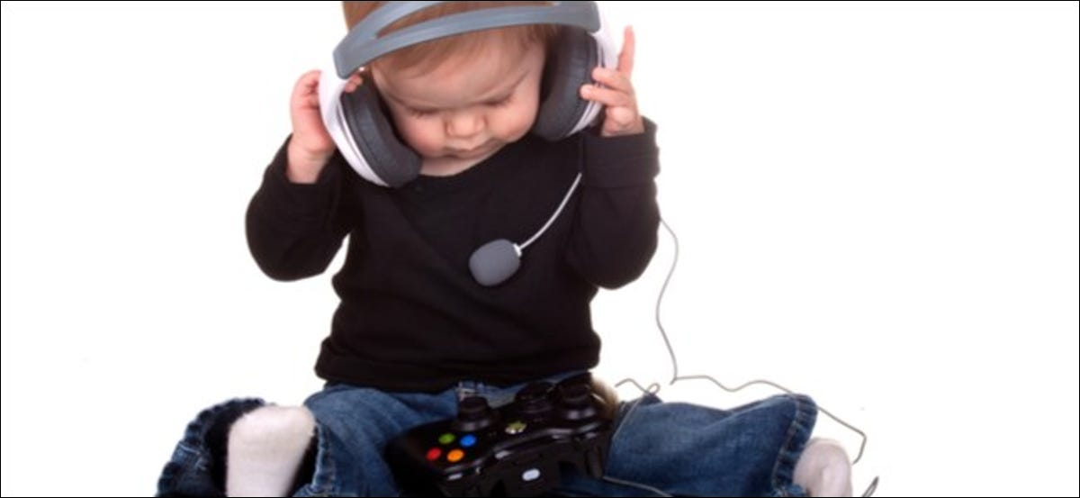 A toddler wearing a headset with an Xbox Controller in his lap.