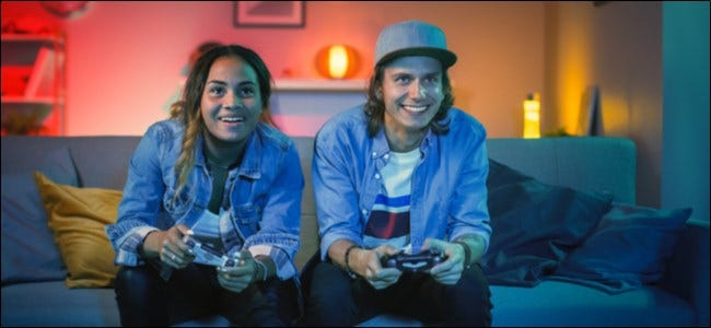 A man and woman sitting on a couch playing a video game.