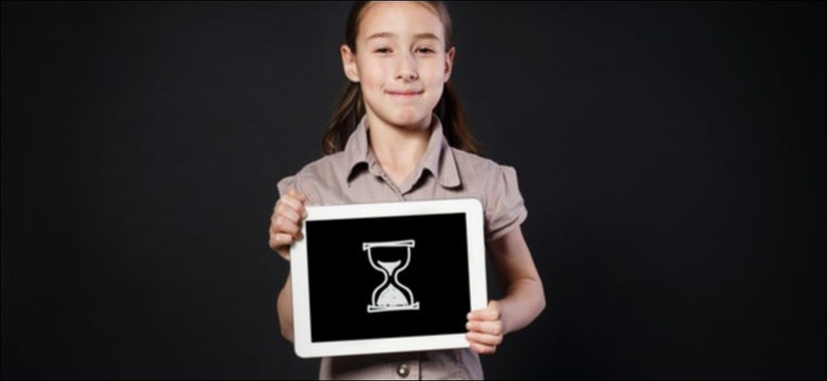 Young girl holding a tablet with a digital drawing of an hourglass on it.