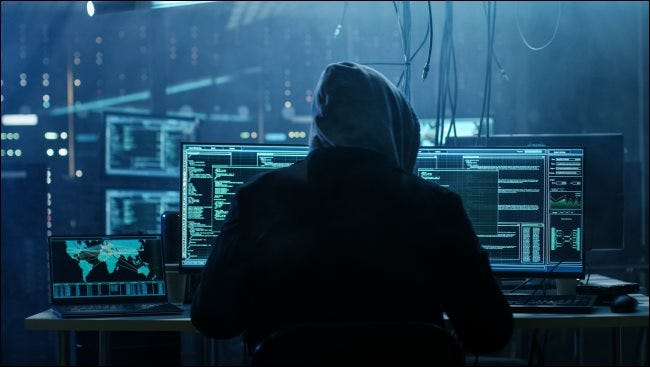A shadowy hacker in a hoodie sitting in front of a computer.