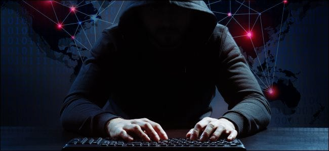 A hoodie-clad hacker typing on a keyboard with a map of the world in the background.