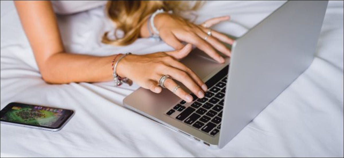 A woman using a MacBook on a bed, which is bad for cooling.