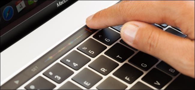 A hand touching the touch bar on a MacBook Pro.