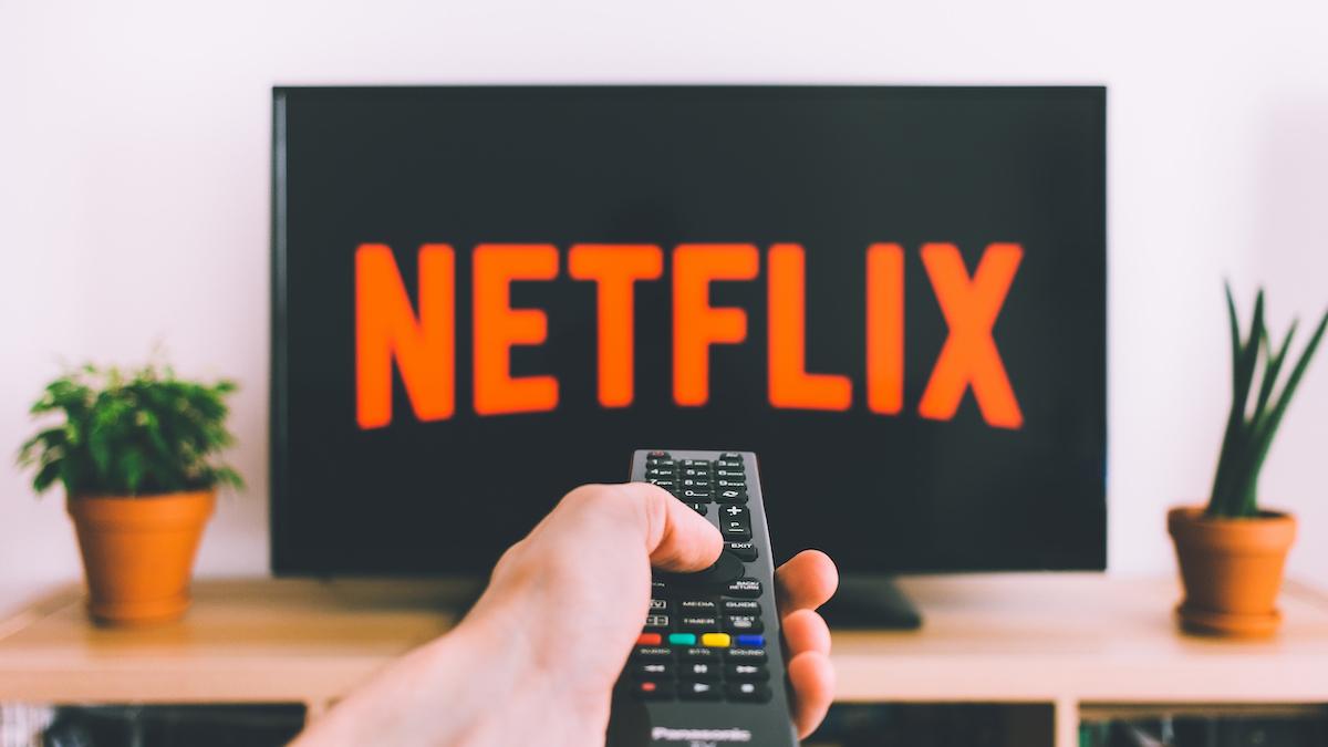 Persona che punta un telecomando verso una TV con il logo Netflix