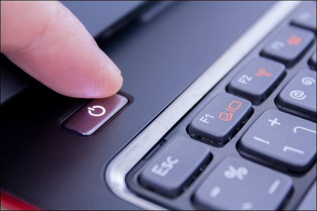 A finger pushing a PC laptop's power button to shut it down.