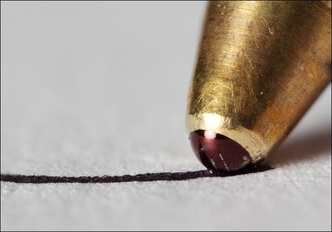 A macro photo of the tip of a ballpoint pen writing on a piece of paper.