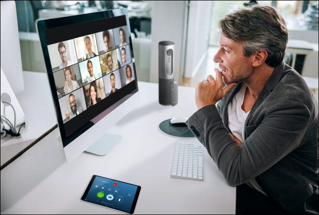 A man on a Zoom Meeting on his Mac with the participants in Gallery View on the monitor.
