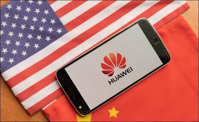 A Huawei phone between a USA and Chinese flag.