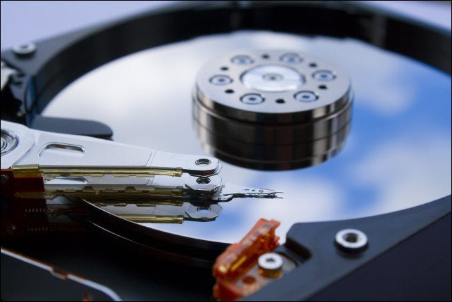 A close-up of a mechanical computer's hard drive platter and head.