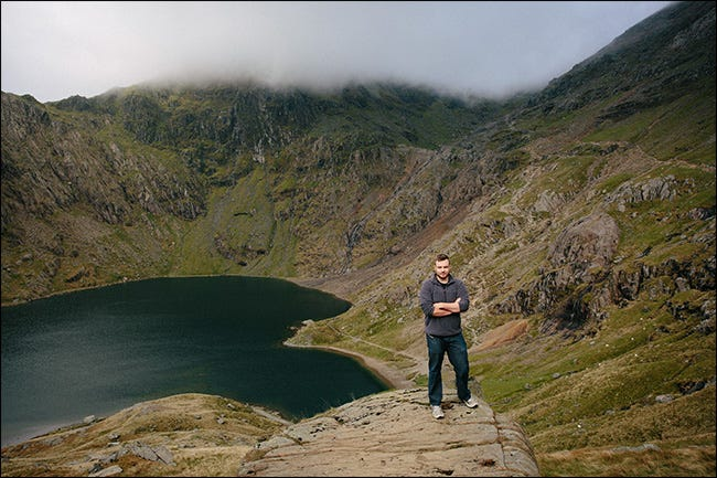 A wide portrait of a man standing in a canyon near a lake.
