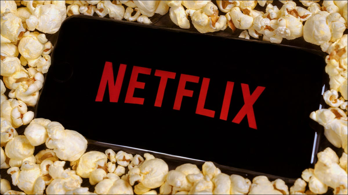 The Netflix logo on a smartphone sitting on a pile of popcorn